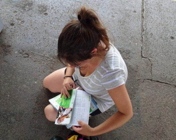 ragazza inginocchiata per terra mentre scrive su un pass le tratte del suo itinerario interrail in Centro Europa