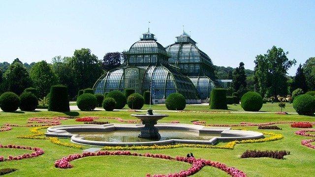 giardino fiorito con una serra e una fontana nel parco di schonbrunn, una delle migliori cose da vedere a Vienna