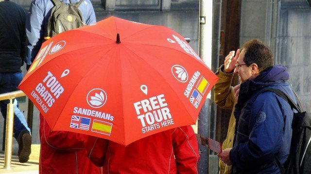 persone che parlano ad un ragazzo che regge un ombrello rosso con la scritta Free Tour