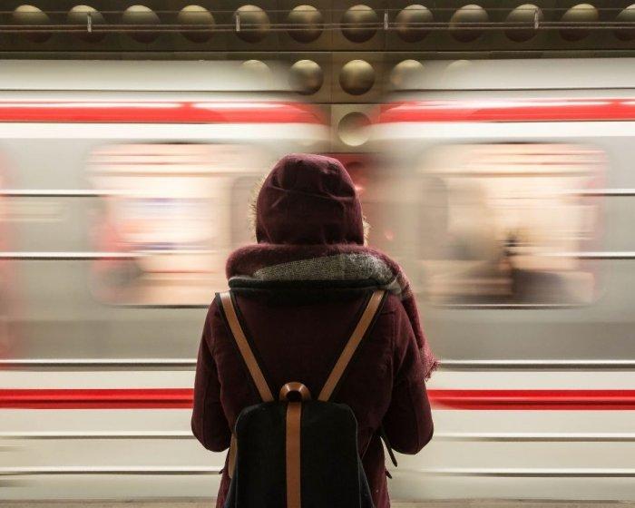 ragazza di spalle, con un piccolo zaino che guarda davanti a sè mentre un treno le passa davanti. Partire leggeri è uno dei consigli fondamentali per un viaggio interrail