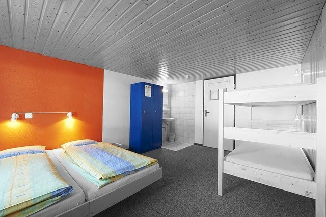 tipica camerata da quattro di un ostello, con un letto a castello e due letti singoli vicini, un lavabo e un locker per gli oggetti di valore