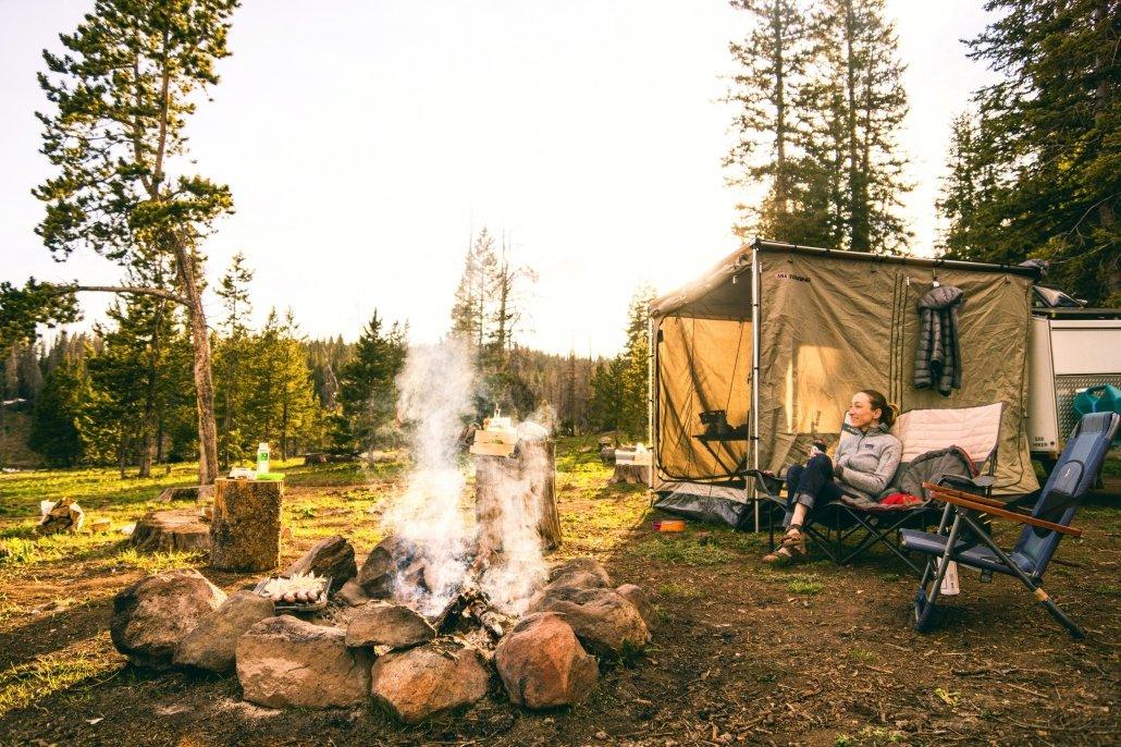 donna seduta da una sedia vicino ad una tenda da campeggio sclta per l'occasione, mentre gurad un falò acceso davanti a lei