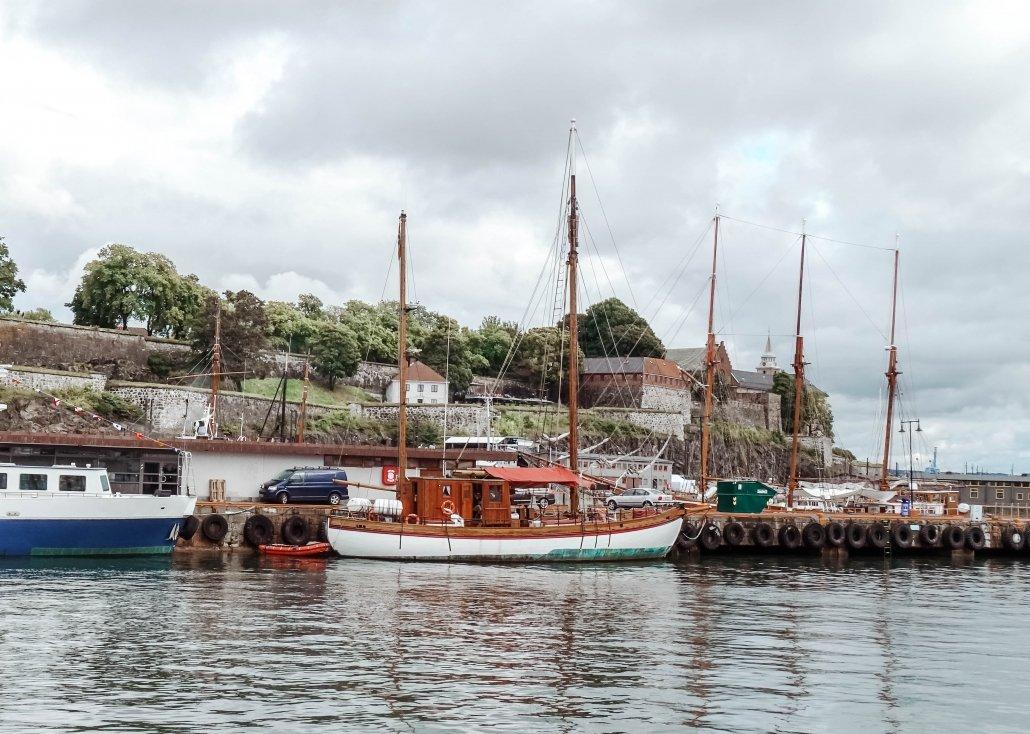 Due barche a vela, una biancaa e marrone e una bianca e blu, ormeggiate davanti ad un molo, con alle spalle la fortezza di Akershus adagiata sulla collina.