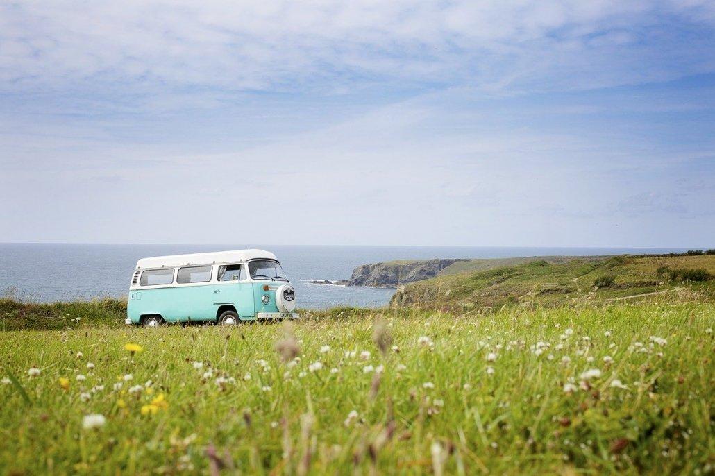 camioncino binaco e verde acqua parcheggiato in un prato con dei fiori bianchi e gialli, con alle spalle il mare ed una scogliera